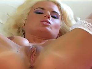 Big boobed milf in panties and stockings plays with her shaved pussy